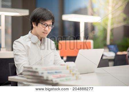 Young Asian man university student working with laptop computer and choosing books for research in library self learning and college lifestyle concepts