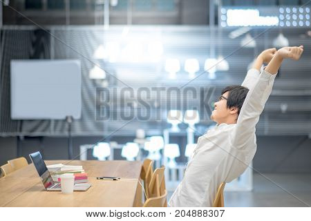 Young Asian man stretching out his arm during working with laptop computer in workspace. High school or university college student educational concept