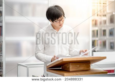 Young Asian man university student reading recommended book on podium in library education research and self learning in college life concepts