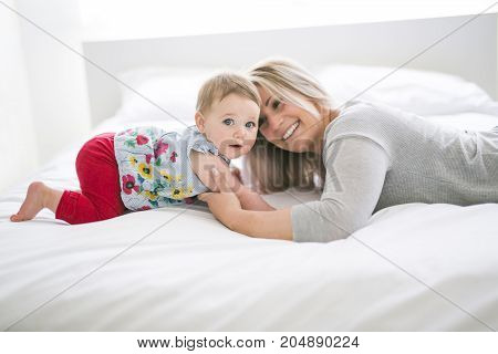 A Pretty baby sit on mom in silk bed
