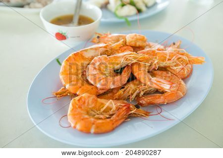 Boiled shrimp with spicy sauce on blue dish