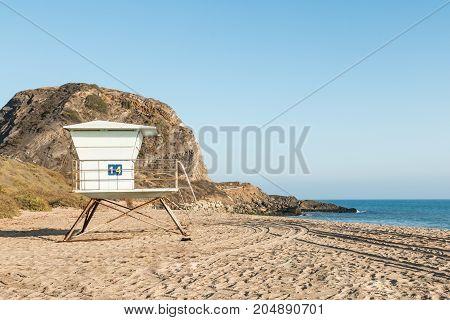 A lifeguard tower at Point Mugu State Park in Malibu, California with Mugu Rock in the background.