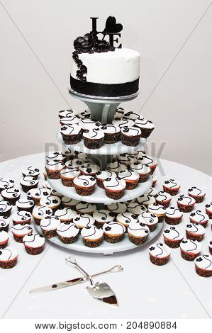 a white and black wedding cake and cupcakes.