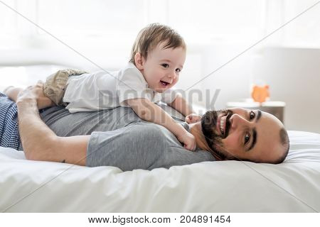 A Beautiful man and son lying together on a bed