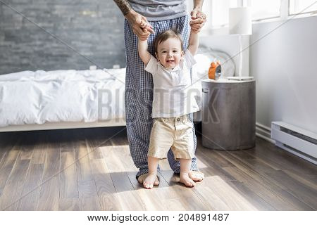 A Father teaching a baby to walk in the bedroom at home