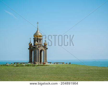 Orthodox Church with Golden domes on the banks of the sea. A symbol of Orthodoxy in the hills and the sea.