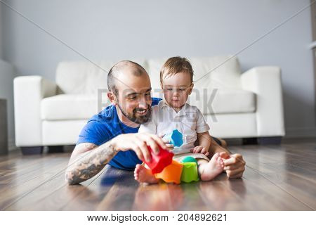 A family, childhood, creativity, activity and people concept - happy father and little son playing with toy blocks at home