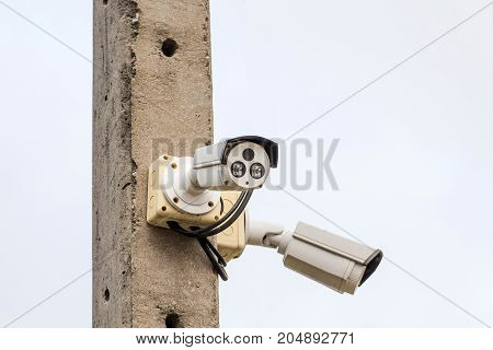 A cctv camera on electric pole watches down below important events