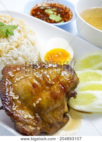 rice topping grilled chicken with teriyaki sauce egg cucumber coriander soup and spicy sauce isolated on white background. closeup
