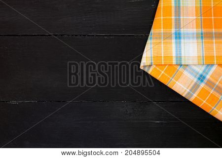 The plaid tartan tablecloth on black wooden table in top view