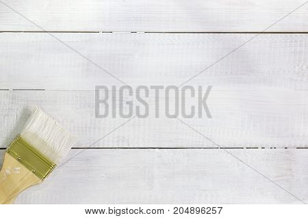 paint brush over white painted wooden surface wood background