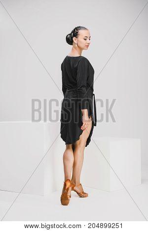 pretty woman in black dress in studio, dancer turning backwards