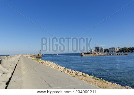Bay view of the port town of Tomis, Constanta. Small Constanta harbour gateway view. Sea wall for protect the beach. Breakwaters concrete tetra-pods.