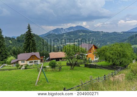 Countryside view in Transylvania. View from above of a village in the Romanian countryside. Mountains and cloudscape in the background