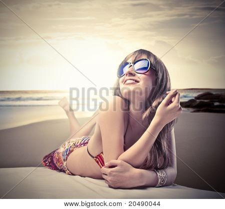 Smiling beautiful woman in bikini lying on a beach