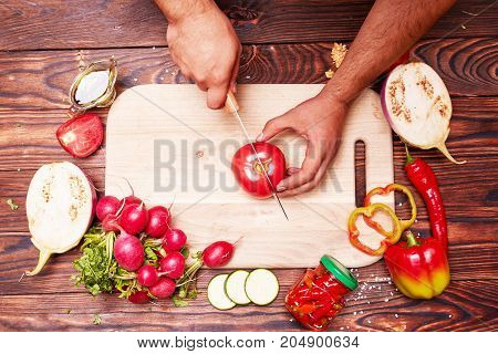 View from above of male chef cutting healthy, red tomato on a cutting desk on a colorful background. Vegetable salad preparation composition.