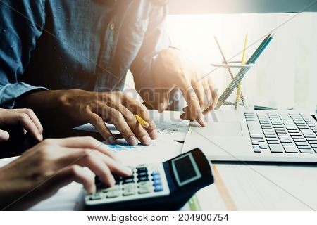 Business People Using Calculator And Laptop Computer For Discussion About Profit, Tax, Financial