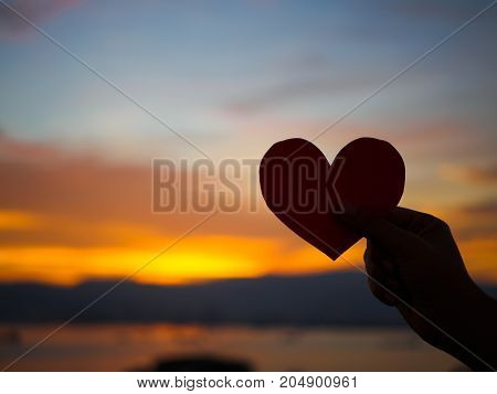 Silhouette hand is raising the red paper heart with blur sunlight during sunset Valentines day.