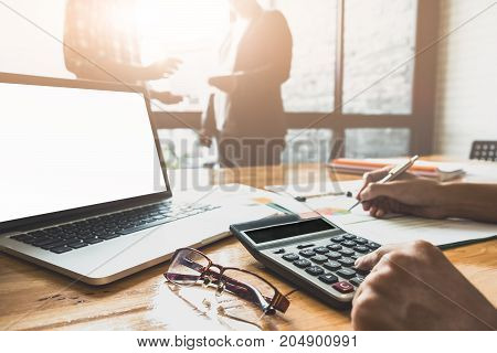 Close Up Businessman And Partner Using Calculator And Laptop For Calaulating Finance, Tax, Accountin