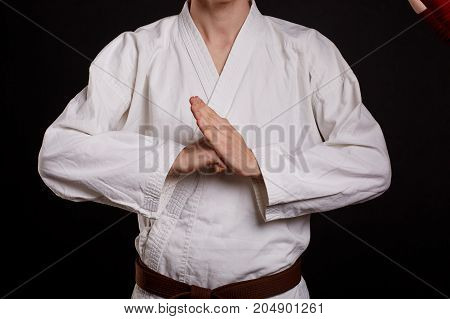 Close-up of a karate student in white kimono with a brown belt on a black background. Karate fighter showing break sign.