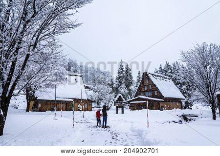 Gifu Japan - December 12 2013: Tourists taking photos in Shirakawago world heritage village the tourist destination in winter with snow falling in Gifu Japan