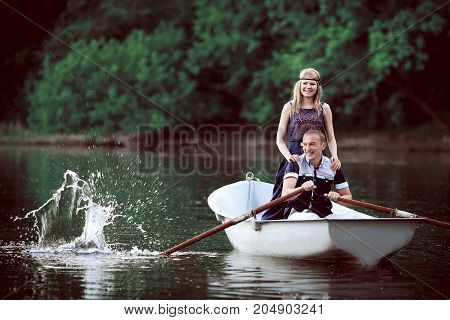 kindly couple rowing on white little boat, girl in blue dress and man in blue shirt and light pants on river, kindly people floating