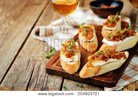Bacon onion marmalade Brie crostini on a wood background