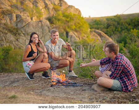 A group of four students relaxing on a picnic day in a national park on a natural background. Young hikers eating roasted marshmallows near the bonfire. Couples on a double-date. Copy space.