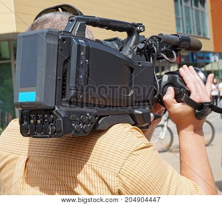 Cameraman at work on the street in summer