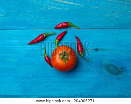 Small hot chili peppers on a blue wooden background. The concept of a healthy lifestyle.