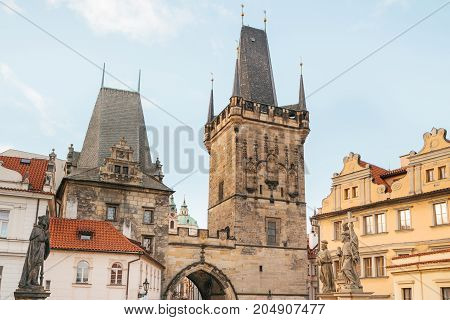 The tower at the entrance to the world famous Charles Bridge in Prague in the Czech Republic. It is a medieval bridge in Prague across the Vltava River, connecting the historic districts of Mala Strana and the Old Town.