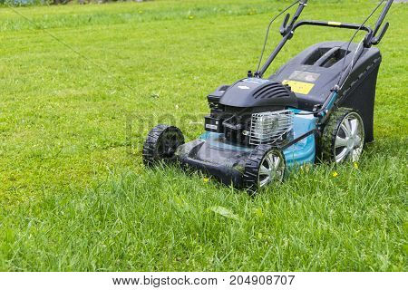 Mowing lawns. Lawn mower on green grass. mower grass equipment. mowing gardener care work tool close up view sunny day