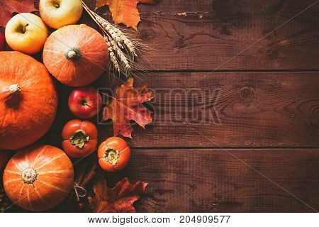 Thanksgiving background: pumpkins, apples, wheat, maple leaves, cones and spices on brown wooden background. Seasonal fall background for Thanksgiving or Halloween. Design mock up. Horizontal