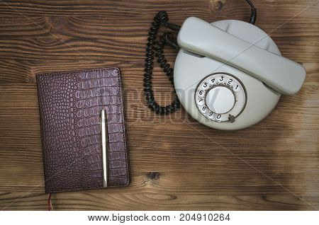 Old telephone phone book and pen on wooden table surface. Contact us.