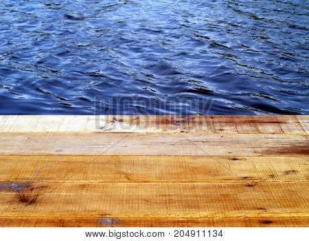 close up old wooden plank of waterfront terrace and beautiful small ripples on blue water surface, corner for relaxing