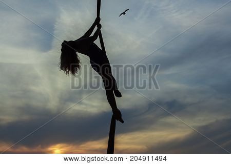 Woman aerial acrobat dances in the air against the sky she demonstrates the tricks.