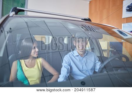 Visit the showroom. Beautiful couple looking at the car and smiling while sitting in his new car.