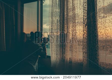 man is taking pictures in the window at sunset