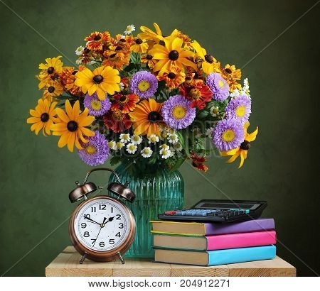 The teacher's day. Autumn bouquet alarm clock electronic calculator and textbooks. Still life on the theme of the first of September knowledge day.