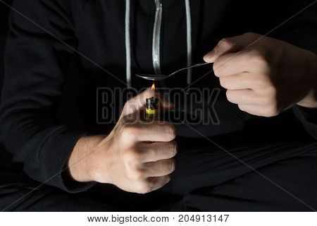 The young man prepares drugs with spoon and lighter