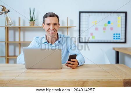 Express positivity. Delighted brunette keeping smile on his face and holding telephone in left hand while looking straight at camera