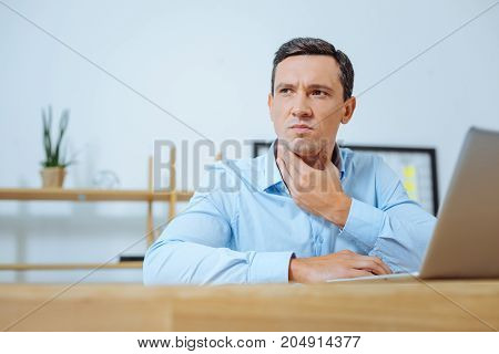 Let me think. Attentive male person wrinkling forehead and touching neck while using his computer