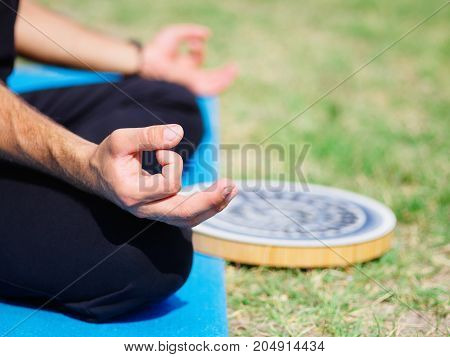 Meditation of yogis in the city park against the background of green trees. Healthy lifestyle.