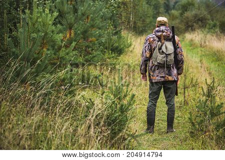 Hunter with a backpack and a hunting gun in the autumn forest.