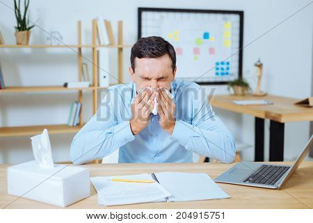 Covering face. Sad brunette man putting elbows on the table and pressing eyes while sneezing