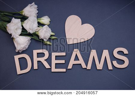 Dreams wooden letters with flowers. Spring dreams. Concept dreams on blue background.