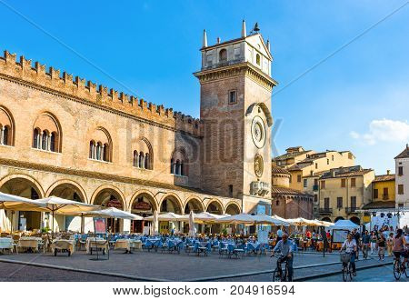 Mantova Italy - July 31 2011: People in in Delle Erbe square with the Della Ragione Palace in the background