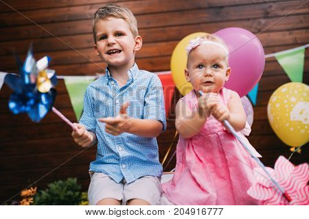 Happy young boy and cute little girl at birthday party