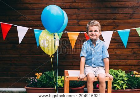 Portrait of young pretty boy sitting on table at birthday party