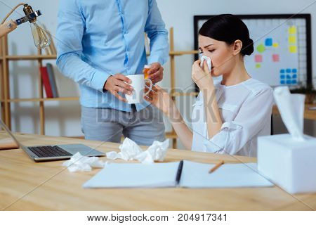 Give it to me. Serious woman covering her nose and sitting in semi position while taking white cup